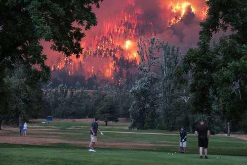گلف بازی در کنار آتش سوزی جنگلی در ایالت واشنگتن در شمال غرب آمریکا