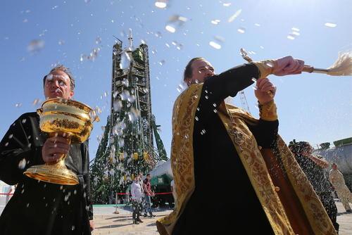 کشیش ارتدوکس در حال اجرای مراسم مذهبی برای راکت فضا پیمای سایوز روسی پیش از پرتاب آن به سمت ایستگاه فضایی بین المللی- پایگاه فضایی بایکونور قزاقستان