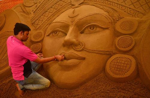 هنرمند هندی در حال درست کردن مجسمه شنی برای جشنواره آیینی