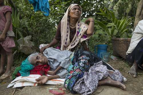 پناهجویان مسلمان میانماری در حال استراحت در کنار جاده در منطقه ای مرزی درون خاک بنگلادش