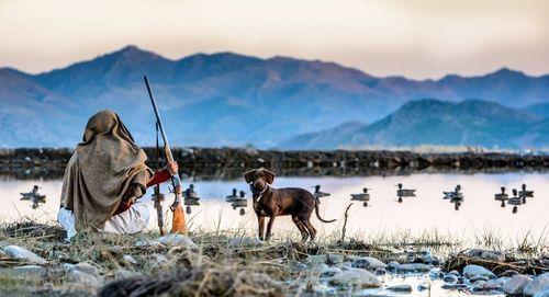 یک شکارچی اردک در حال رصد حرکت اردک های مهاجر سیبریایی در دریاچه ای در مرز پاکستان و افغانستان / عکس روز وب سایت