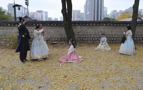 گردشگران کره ای با لباس سنتی در حال گرفتن عکس در کاخی در سئول