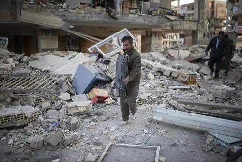 برداشتن وسایل خانه از زیر آوار خانه ها در شهر زلزله زده سرپل ذهاب