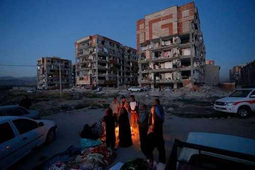 گرم شدن مردم زلزله زده سرپل ذهاب با آتش در کنار خانه های متروک و مخروب/عکس: پوریا پاکیزه؛ خبرگزاریEPA
