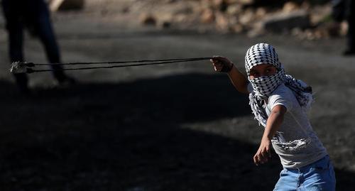 نوجوان فلسطینی در حال پرتاب سنگ به سمت نظامیان اسراییلی- نابلس