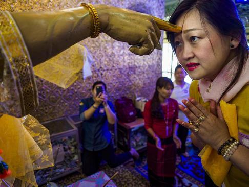 زن بودایی در معبدی در شهر یانگون میانمار