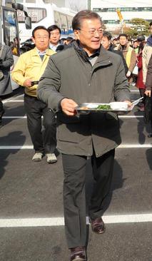 رییس جمهور کره جنوبی در حال حمل سینی ناهارش به داخل استادیوم شهر زلزله زده پوهانگ به منظور دیدار با خانواده های زلزله زده/ خبرگزاری یونهاپ کره جنوبی