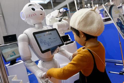بازی یک کودک با روبات انسان نمای سافت بانک ژاپن ( به نام پِپِر) در نمایشگاه سالانه روبات در توکیو