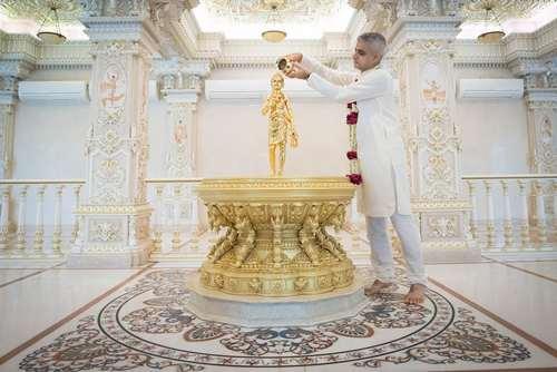 شهردار لندن در حال ریختن آب مقدس روی مجسمه ای طلایی در معبدی در دهلی نو هند