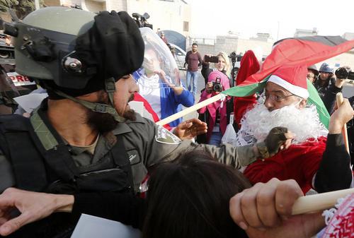 با نزدیک شدن کریسمس فلسطینی های معترض به تصمیم جنجالی ترامپ در انتقال سفارت آمریکا از تل آویو به قدس با لباس بابانوئل به مصاف سربازان اسراییلی می روند./ بیت لحم