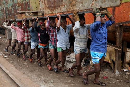 کارگران بنگلادشی در حال حمل یک قطعه آهنی سنگین- داکا
