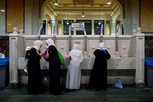 زنان در حال پر کردن بطری هایشان از آب زمزم در مسجد الحرام مکه