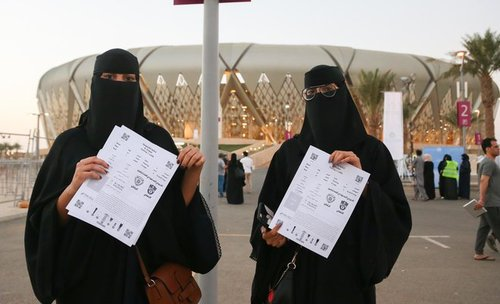دو خانم سعودی بلیط مسابقه را خریداری کرده اند و با ورزشگاه شهر جده عکس یادگاری انداخته اند.