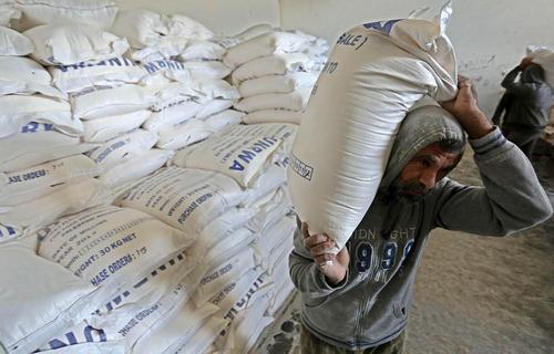 بارگیری کیسههای آرد از مرکز توزیع غذای سازمان ملل در منطقه خان یونس در باریکه غزه