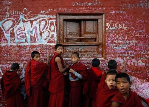راهبان نوجوان بودایی در حال نگارش روی دیوار یک معبد در جریان یک جشنواره آیینی- کاتماندو نپال
