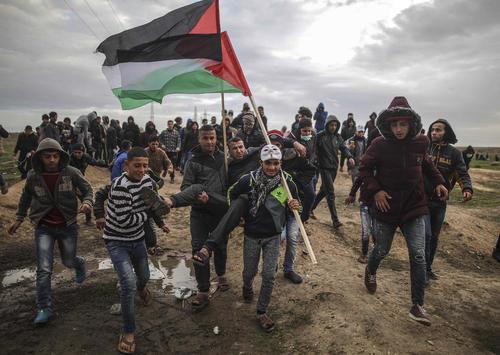 جوانان فلسطینی در حال حمل یک مجروح در جریان اعتراضات هفتگی در مرز باریکه غزه و اسراییل