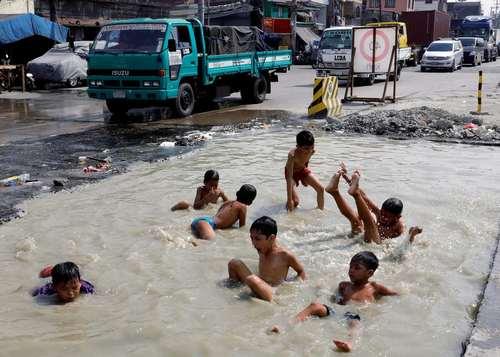 آبتنی کودکان در یک چاله آب در شهر تندو فیلیپین
