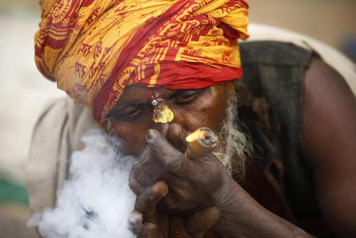 یک راهب هندو در حال کشیدن ماریجوانا در جشنواره آیینی