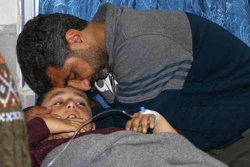 در آغوش گرفتن فرزند مجروح شده در اثر بمباران شهر عفرین سوریه در بیمارستانی در این شهر/عکس: