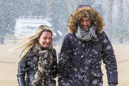 یک زوج انگلیسی زیر بارش برف در شهر لندن