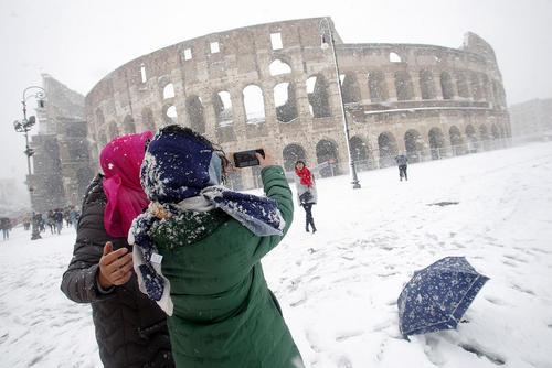 گردشگران در حال عکس گرفتن زیر بارش برف در شهر رم ایتالیا