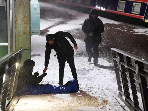 کمک به یک بیخانمان در سرما و برف شهر بیرمنگام انگلیس