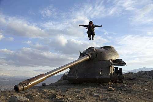 پریدن یک پسربچه از روی یک تانک اسقاط شده روسی در حومه شهر کابل افغانستان/ عکس: آسوشیتدپرس