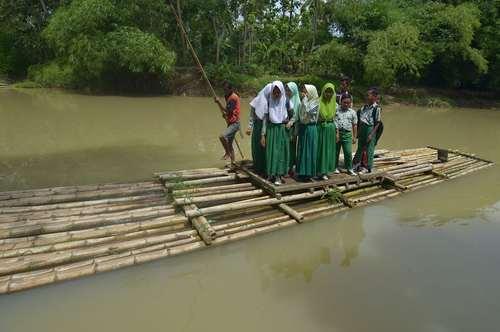 دانش آموزان اندونزیایی برای عبور از عرض رودخانه و عزیمت به مدرسه سوار بر یک قایق الواری چوب بامبو شده اند./ عکس: رویترز