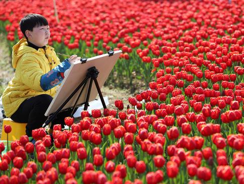 نقاشی یک نوجوان چینی در بوستان گلی در شهر ونلینگ چین/عکس: شینهوا