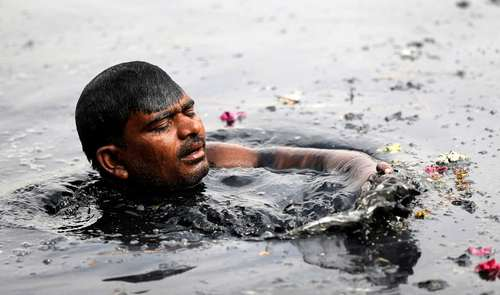 جستجو در آب آلوده رود یامونا برای یافتن نذورات و سکههای پرتاب شده مردم به داخل آن در جریان یک جشنواره مذهبی هندوها- دهلینو