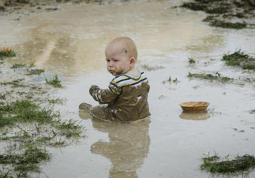 بازی یک نوزاد در گل و لای پارکی در کانتربوری نیوزیلند