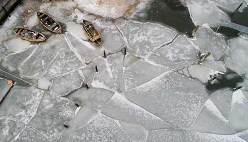 قایق ها در آب های یخ زده بندری در شرق آلمان
