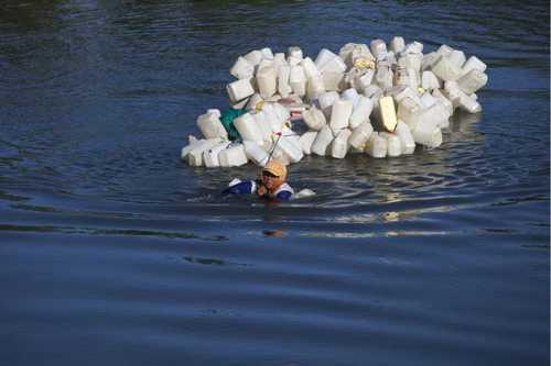 در حال عبور از رود ماندار در اندونزی برای پر کردن 200 ظرف آب معدنی
