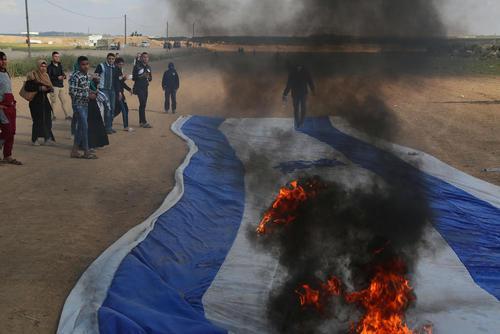 آتش زدن پرچم اسراییل از سوی معترضان فلسطینی در مرز باریکه غزه