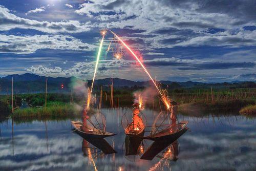ماهیگیران میانماری در حال نورافشانی در جشنواره نور بو ها در دریاچه ای در میانمار- ع روز وب سایت