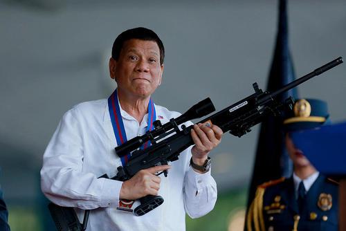 رییس جمهوری جنجالی فیلیپین در آیین تودیع و معارفه رییس جدید پلیس ملی فیلیپین تیربار به دست گرفته است