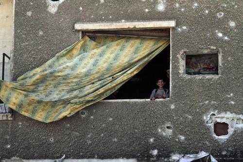 لبخند در خانهای زخمی از گلولههای جنگی در شهر جنگ زده دوما در حومه شرقی شهر دمشق سوریه/ عکس: شینهوا