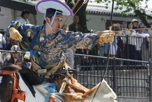 اجرای نمایش یک کماندار روی اسب در لباس سنتی ژاپنی در پارکی در توکیو