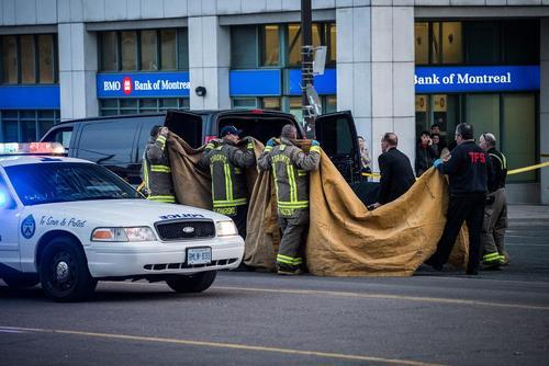 نحوه انتقال جسد قربانیان حمله خودرویی اخیر در تورنتو کانادا. ماموران منطقه اطراف برانکارد انتقال جسد را با پارچه پوشاندهاند؛ ازدحامی هم در کار نیست./ عکس:آرون وینسنت؛ کانادا پرس