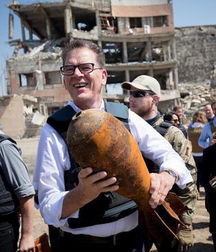 به دست گرفتن پوکه خمپارهای باقی مانده از دوران جنگ از سوی وزیر توسعه آلمان در مقابل بیمارستانی تخریب شده به دست داعش در شهر موصل عراق/ عکس: خبرگزاری آلمان