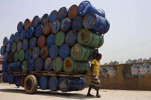 یک کارگر در حال حمل انبوهی از بشکه - داکا