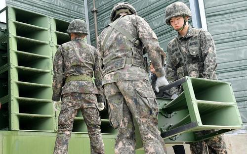 سربازان کره جنوبی در حال پایین کشیدن و جمع کردن بلندگوهای تبلیغاتی ضد حکومت کره شمالی از منطقه مرزی مشترک دو کره/ عکس: یونهاپ
