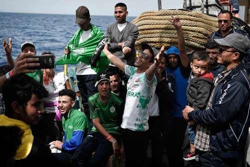 شادمانی پناهجویان مراکشی عازم اروپا در دریای مدیترانه از رسیدن تیم امدادی اروپا در 25 مایلی سواحل لیبی/خبرگزاری فرانسه