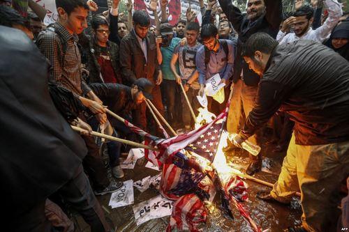 عکس خبرگزاری فرانسه از آتش زدن پرچم آمریکا از سوی گروهی از بسیجیها در مقابل سفارت سابق آمریکا در تهران