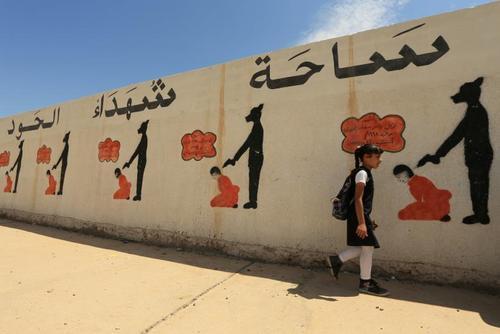 نقاشیهای دیواری یک مدرسه در شهر موصل عراق که نشان دهنده روشهای جنایت داعش در کشتار زندانیان است./ رویترز