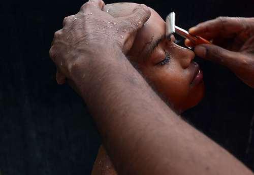 تراشیدن موها و ابروهای یک راهب نونهال در سریلانکا