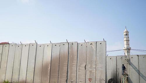 عبور جوان فلسطینی از دیوار حائل بین کرانه غربی و شهر قدس برای رفتن به سومین نماز جمعه ماه رمضان در مسجد الاقصی