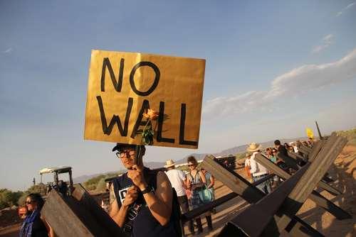 فعال آمریکایی مدافع حقوق مهاجران در منطقه مرزی بین مکزیک و آمریکا در اعتراض به احداث یک دیوار 34 کیلومتری مرزی بین دو کشور پلاکارد بلند کرده است./خبرگزاری فرانسه