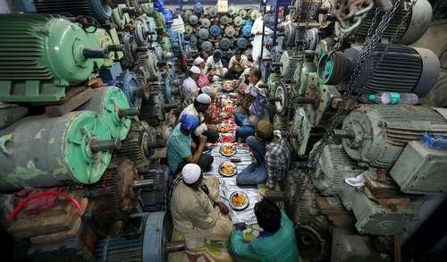 کارگران مسلمان در داخل یک مغازه فروش پمپ آب در شهر دهلینو هند در حال افطار هستند./عکس: EPA