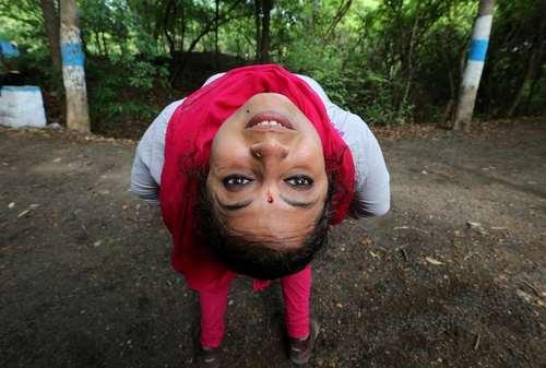 یک زن هندی در حال تمرین یوگا در پارکی در